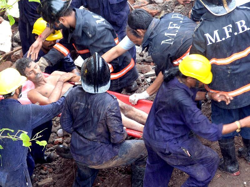 Firefighters and rescue workers bring out a survivor from under the rubble of a collapsed building in Mumbai (AFP Photo)
