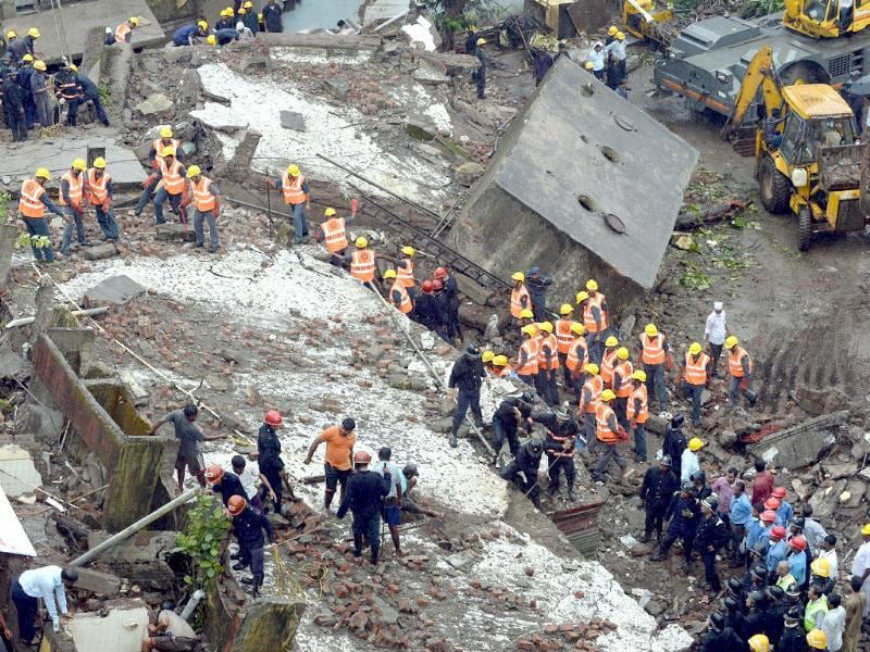 Firefighters and rescue workers are seen searching for survivors at the site of the collapsed building in Mumbai. (AFP Photo)