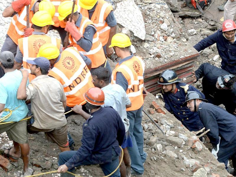 Firefighters (bottom right) look through a gap as they search for survivors at the site of the collapsed building in Mumbai. (AFP Photo)
