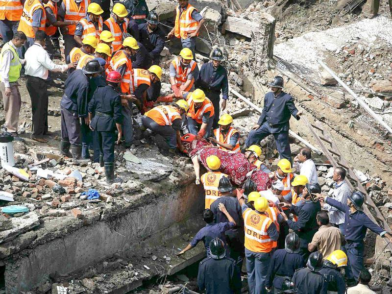Rescue workers recover a body from the debris at the site of a collapsed residential building in Mumbai. (Reuters Photo)