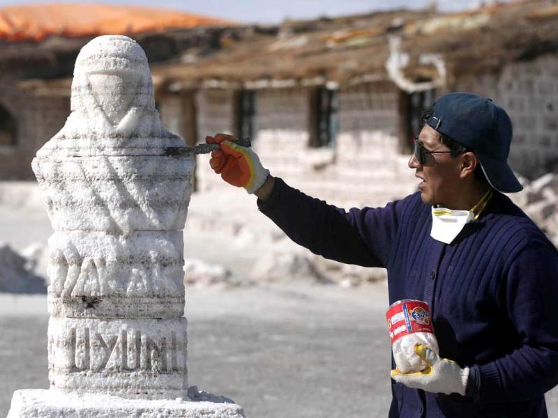 A man works on a salt sculpture, symbolising the Dakar race, at the Salt flat in Uyuni, in Bolivia. (Reuters Photo)