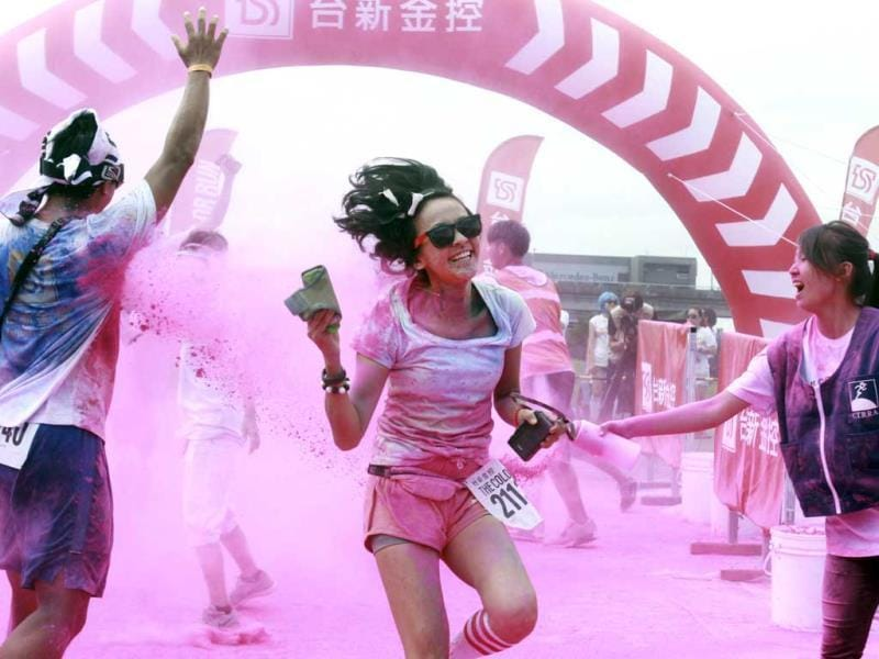 Runners covered with color powders pose for photos during the Color Run at the Dajia Riverside Park in Taipei, Taiwan. (AP Photo)