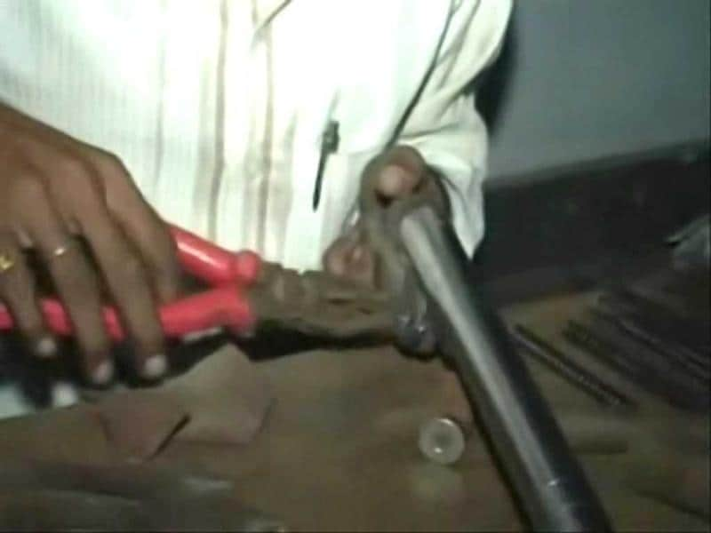 A craftsman fits the barrel of a countrymade pistol in an illegal factory. There is no official estimate but illegal gun factories are spread across Uttar Pradesh. (HT photo)