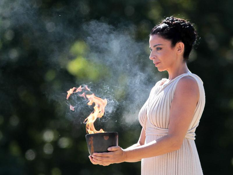 Actress Ino Menegaki as high priestess, carries the Olympic Flame inside the ancient Olympic stadium after it was lit from the sun's rays, during the final dress rehearsal for lighting of the Olympic flame at Ancient Olympia. (AP Photo)