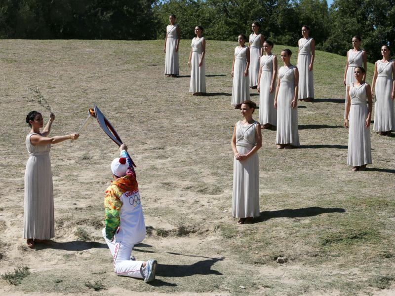 Actress Ino Menegaki as high priestess (L) passes the Olympic Flame to the first torch runner Greek champion skier Giannis Antoniou during the final dress rehearsal at Ancient Olympia. (AP Photo)