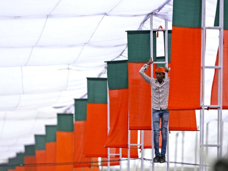 A supporter stands on a pole under a tent to watch Modi addressing his party supporters during a rally in New Delhi. (Reuters Photo)
