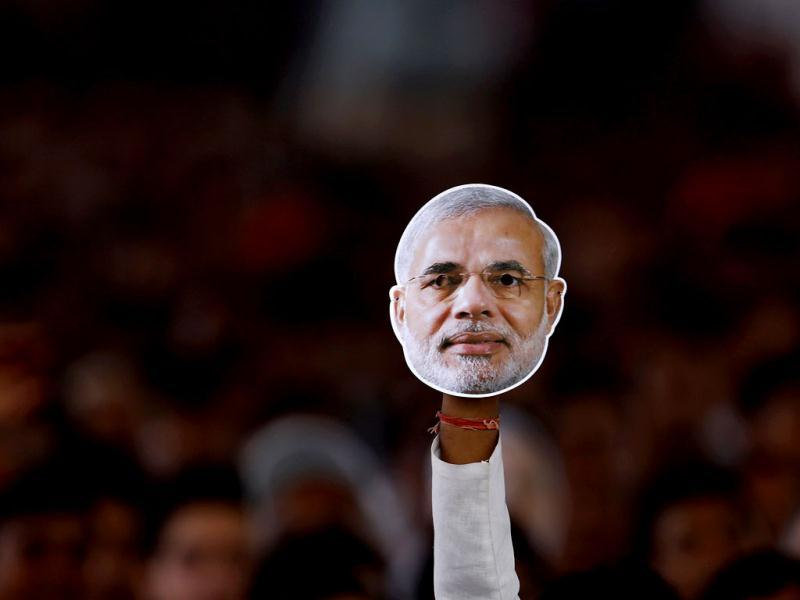 A supporter of main opposition Bharatiya Janata Party (BJP) holds a mask of Narendra Modi. (Reuters Photo)