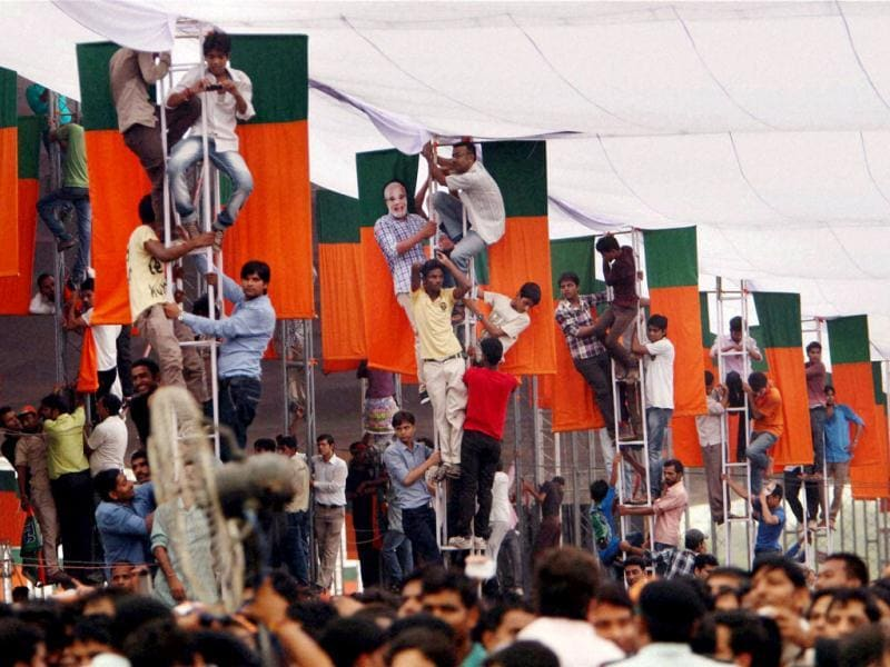 BJP supporters climb on ladders at Vikas Rally in New Delhi. (PTI Photo)