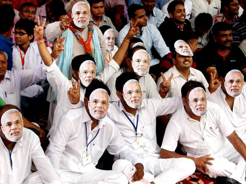 BJP supporters with mask of Gujarat CM and BJPs PM candidate Narendra Modi during Vikas Rally in New Delhi. (PTI Photo)