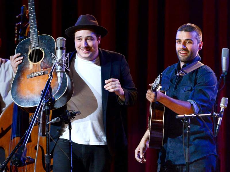Musicians Marcus Mumford (L) and Oscar Isaac perform together during
