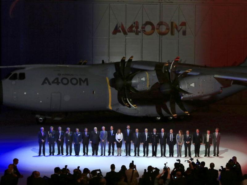 Spain's Crown Prince Felipe (C) poses for a family photo next to an Airbus A400M military transport plane during a ceremony at an assembly plant in the Andalusian capital of Seville. (Reuters Photo)