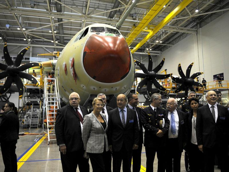 French defence minister Jean-Yves Le Drian (4thL), former French defence minister Michele Alliot-Marie (3rdL) and officials pose as they visit the A400M assembly line during the A400M First Delivery Ceremony in Sevilla. (AFP Photo)