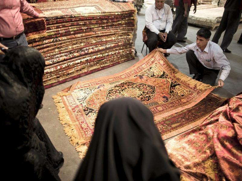 An Iranian man shows his silk carpets to clients at Iran's international hand-woven carpet exhibition in Tehran. (AFP Photo)