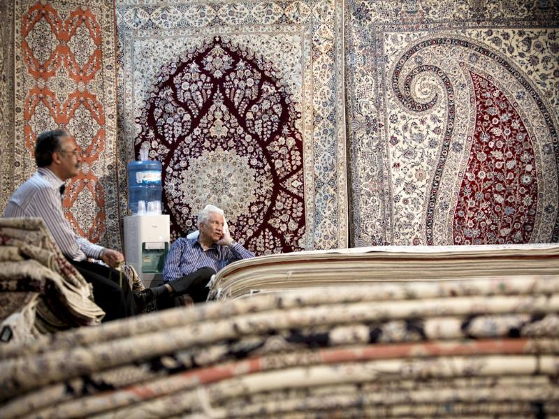 Iranian carpet businessmen sit in their stall at Iran's International hand-woven carpet exhibition in Tehran. (AFP Photo)