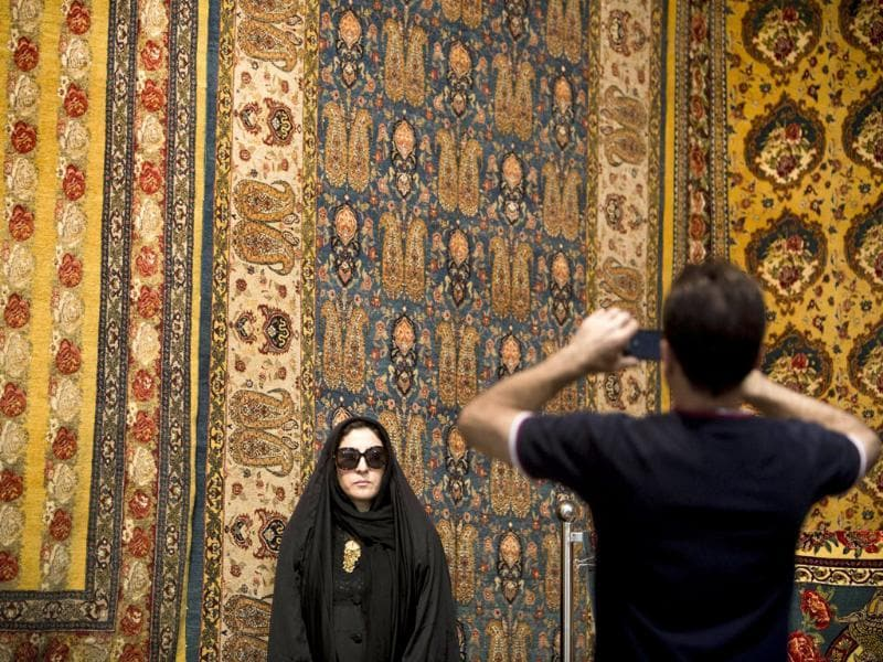 An Iranian man takes a picture of his relative in front of Persian carpets at Iran's international hand-woven carpet exhibition in Tehran. (AFP Photo)
