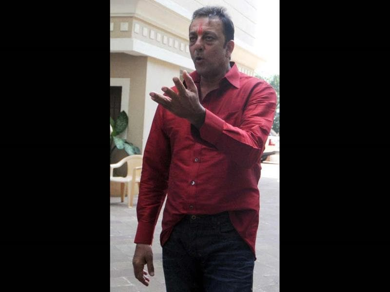 Sanjay Dutt interacts with the media at his residence after arriving from Yerwada prison in Mumbai on October 1, 2013. (AFP)