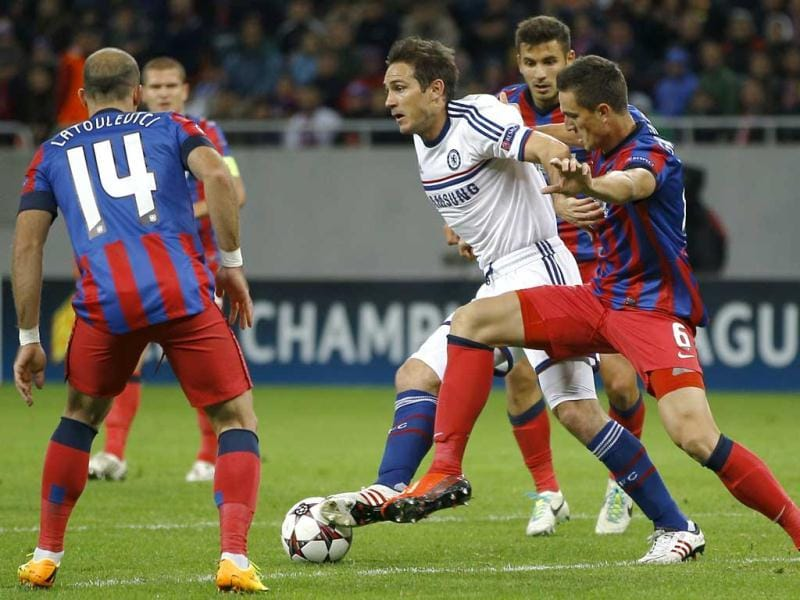 Chelsea's Frank Lampard, center, is challenged by Steaua's Florin Gardos, right, during the soccer Champions League group E match between Steaua Bucharest and Chelsea in Bucharest, Romania. (AP Photo)