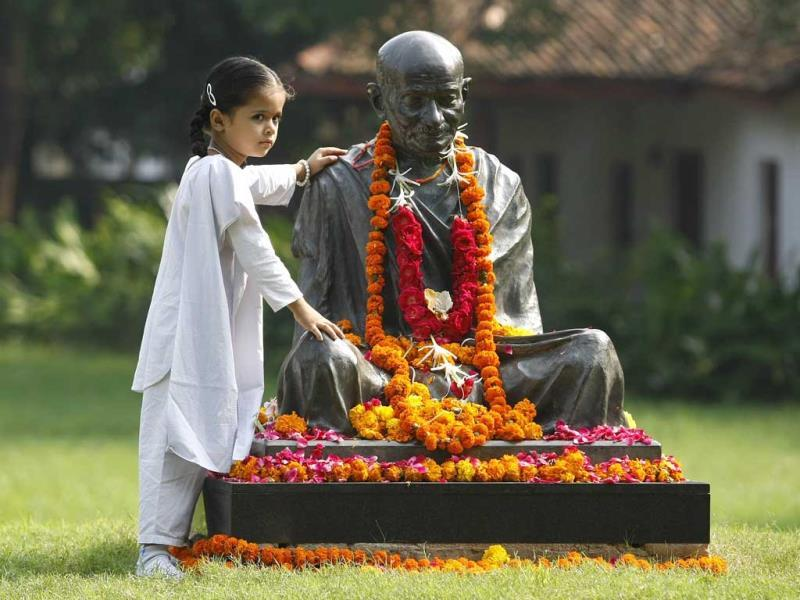 A schoolgirl poses for a picture next to a statue of Mahatma Gandhi during celebrations to mark his 144th birth anniversary at Ahmedabad. (Reuters Photo)