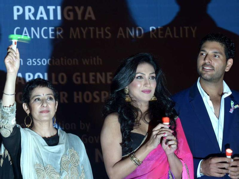 Yuvraj Singh poses with actresses Manisha Koirala and Rituparna Sengupta during a function in Kolkata on October 1, 2013. The function was organised by various NGO's to promote cancer awareness. (AFP Photo)