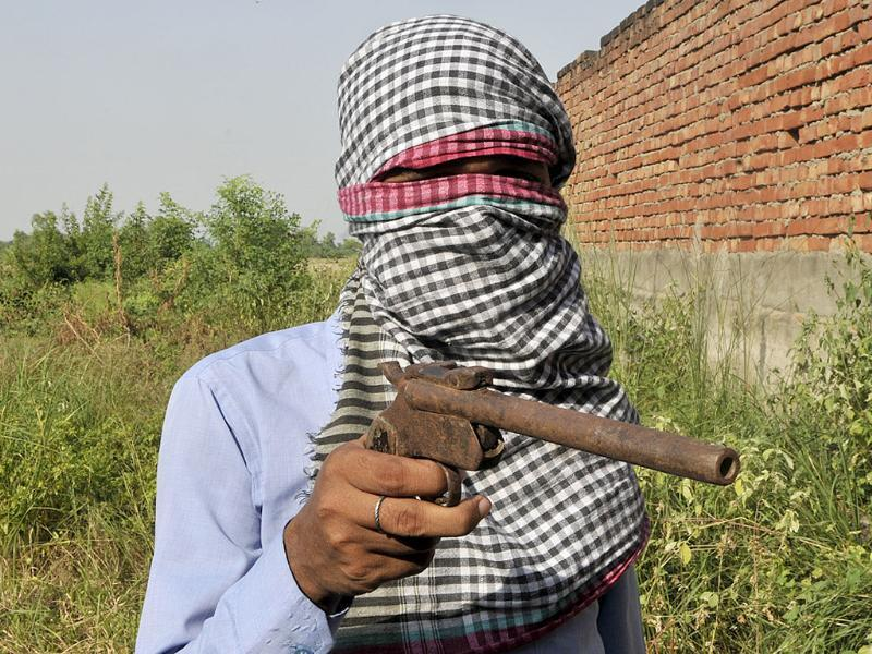 An agent displays a countrymade pistol in a village in Etah. Guns come as cheap as a few thousand rupees in UP. (Vipin Kumar/HT photo)