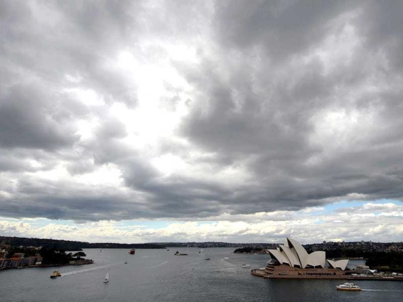 Dark clouds cover the sky over the iconic Sydney Opera House (centre) prior to the arrival of the tall ships on the eve of the International Fleet Review. (AFP Photo)