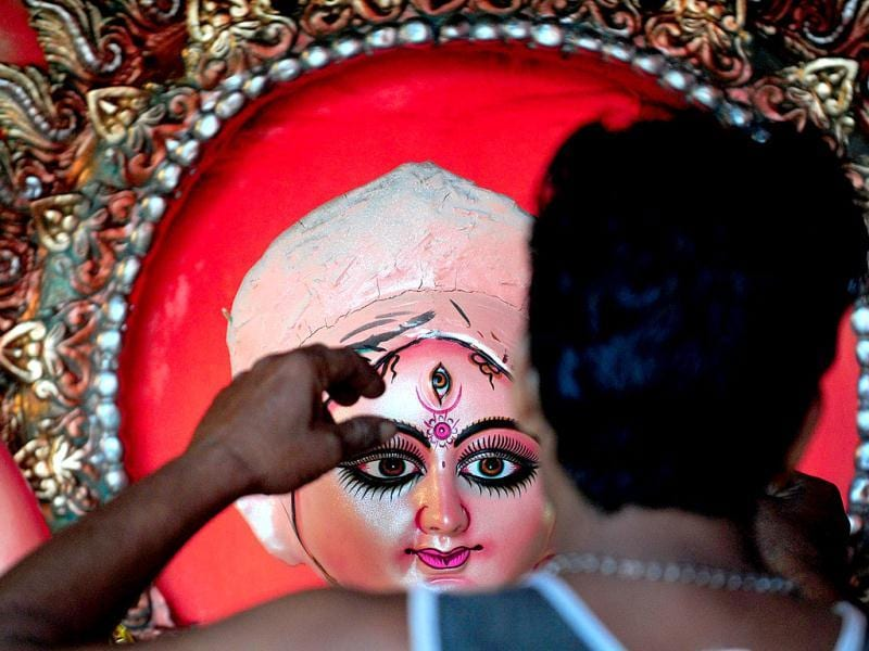An artisan gives the final touches to an idol of goddess Durga ahead of the Durga Puja festival at a workshop in Allahabad. (AFP Photo)