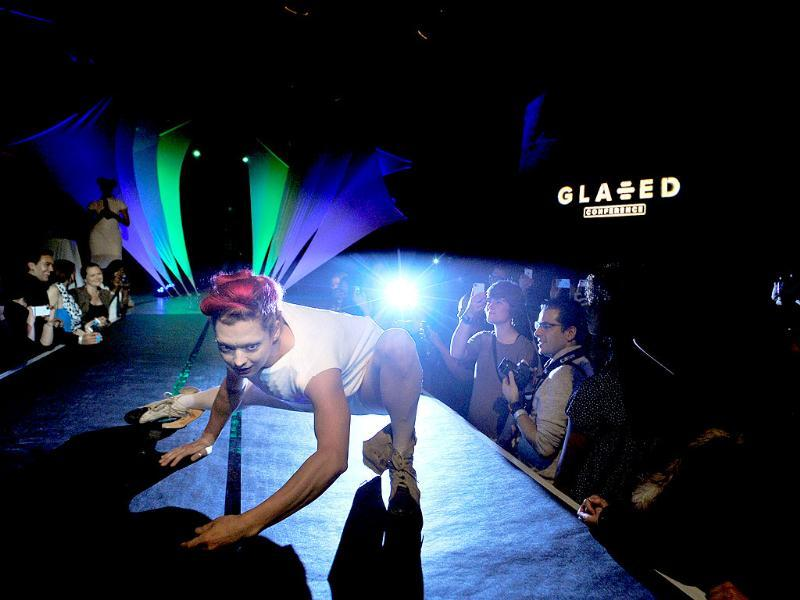 A model contorts her body on a runway while adorning an outfit fitted with LED lights at the Glazed Conference in San Francisco. (AFP Photo)