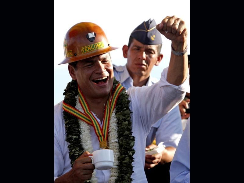 Ecuador's President Rafael Correa wears a miner helmet during his welcome ceremony in Ivirgarzama, Bolivia.(AP photo)