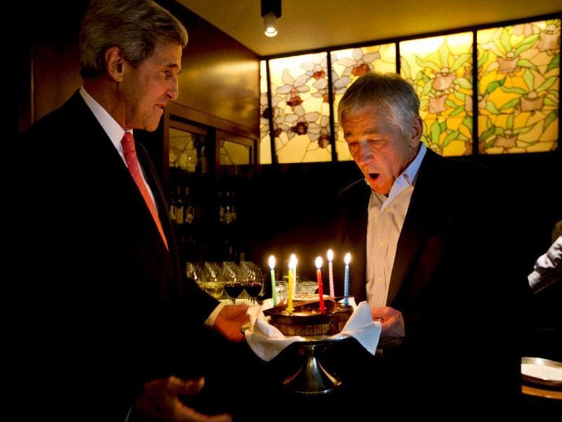 US secretary of defence Chuck Hagel blows out the candles on a surprise birthday cake from US secretary of state John Kerry in Tokyo.(Reuters photo)