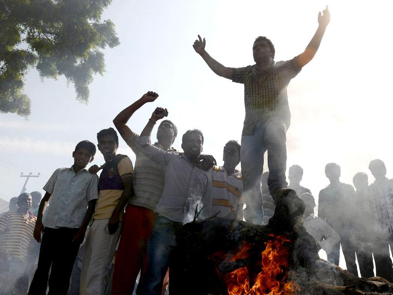 Indian supporters of united Andhra Pradesh shout slogans as they block the road with burning barricades during a protest against the formation of a separate Telangana state in Ananthapuram. (AFP Photo)