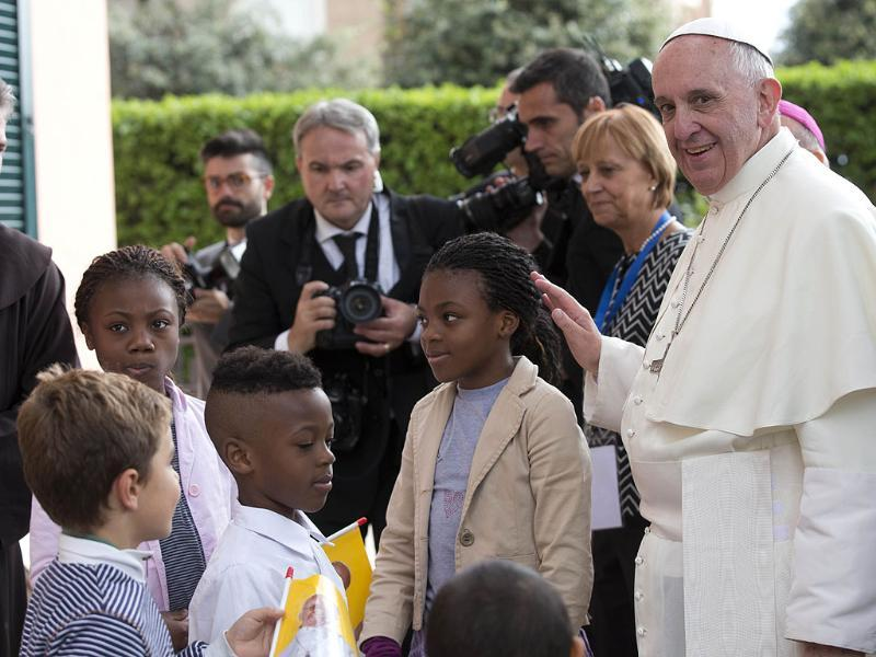 The Pope being welcomed by children as he arrives to lunch with them at St Mary of the Angels, near Assisi, Italy. (AP Photo)