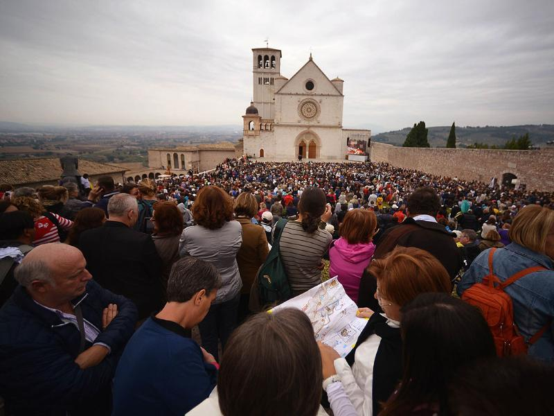 Faithfuls gather outside St Francis Basilica during a papal mass in Assisi for the first-ever visit by Pope Francis. (AFP Photo)
