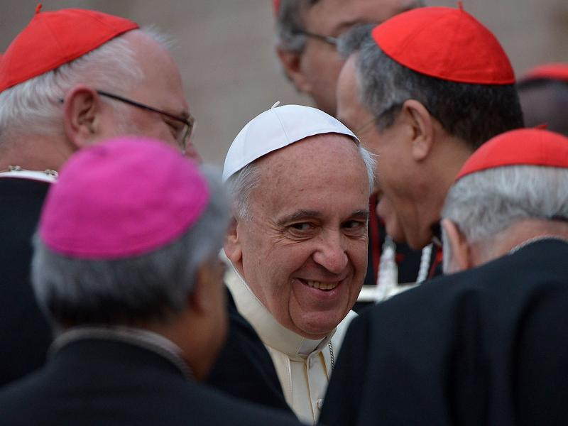 Pope Francis is surrounded by cardinals as he arrives for a pastoral visit at St Francis of Assisi. (AFP Photo)