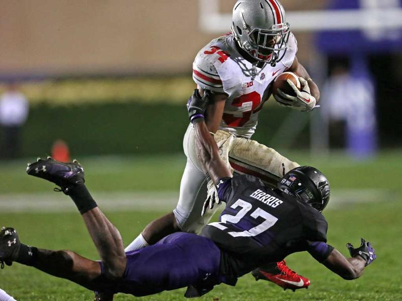 Carlos Hyde #34 of the Ohio State Buckeyes runs over Matthew Harris #27 of the Northwestern Wildcats at Ryan Field in Evanston, Illinois. (AFP/Getty Images)