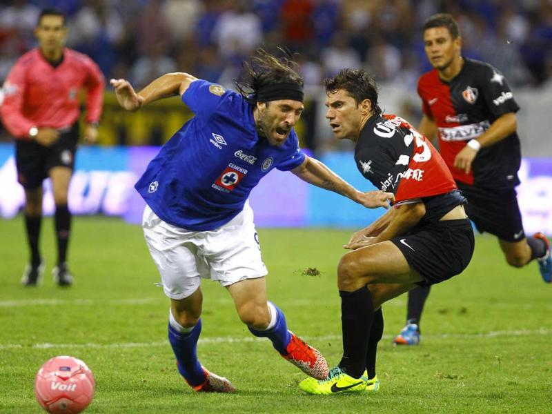 Mariano Pavone of Cruz Azul vies for the ball with Leandro Cufe of Atlas, during their Apertura 2013 Mexican tournament football match in Jalisco Staduim in Mexico. (AFP Photo)