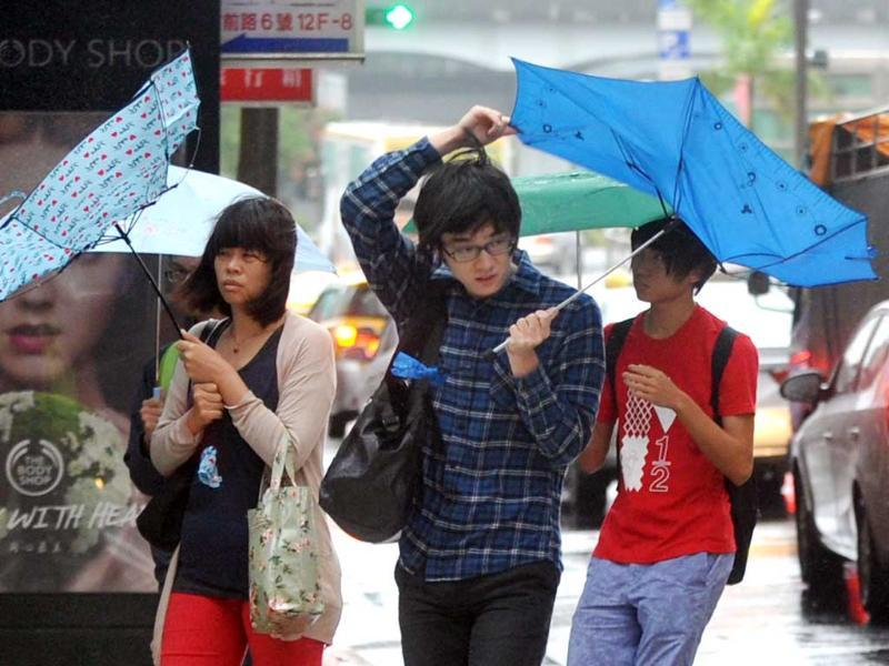 Pedestrians walk through strong winds and rain caused by Typhoon Fitow in Taipei. Taiwan on October 5 issued a warning over Typhoon Fitow. (AFP Photo)