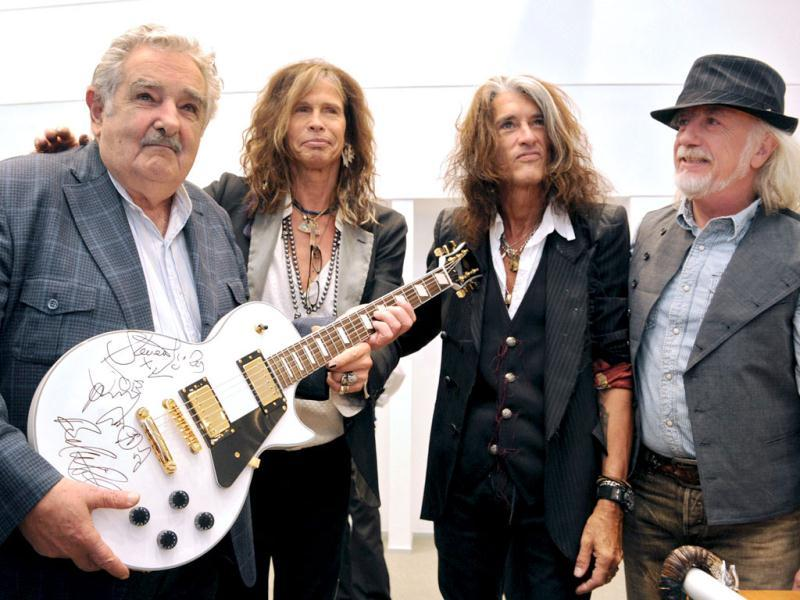 Uruguayan Presidency of Uruguayan President Jose Mujica (L) as he poses with a guitar given to him by US hard rock band Aerosmith's singer Steve Tyler, guitarists Joe Perry (2-R) and Brad Whitford (R) in Montevideo. (AFP Photo)
