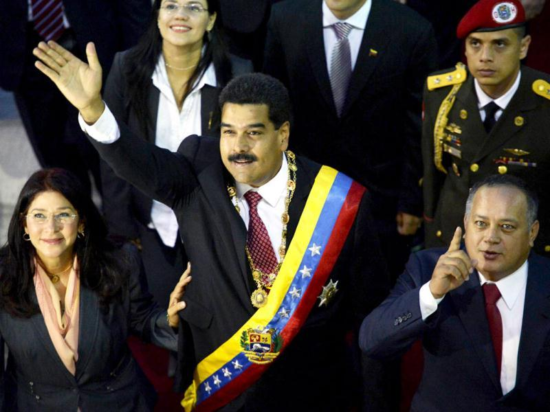 Venezuelan President Nicolas Maduro waves next to Venezuelan First Lady Cilia Flores and the president of the Venezuelan National Assembly, Diosdado Cabello, in Caracas. (AFP Photo)