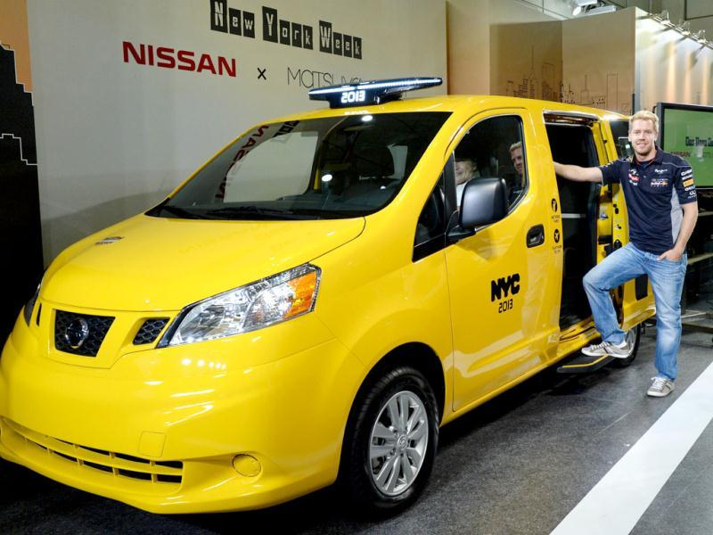 German three-time Formula One champion Sebastian Vettel poses beside Nissan's NV200, 'New York taxi of tomorrow', during its press preview in Tokyo. (AFP Photo)