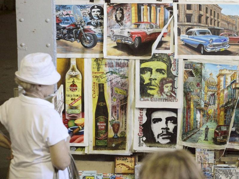 Tourists look at artwork based on images of revolutionary leader Che Guevara at an artisans' fair in Havana. (Reuters Photo)