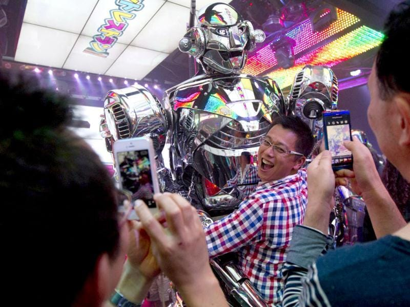 A customer hugs a robot as his friends photograph him after the show at Robot Restaurant in Tokyo. (AP Photo)