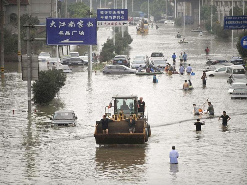 Residents travel on a bulldozer as others walk amid a flooded street after Typhoon Fitow hit Yuyao, Zhejiang province. (Reuters Photo)