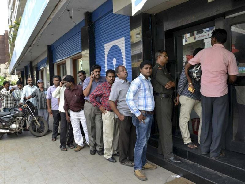 People queue up at an ATM after majority of the ATMs stopped working following power outages in Visakhapatnam.(AP Photo)
