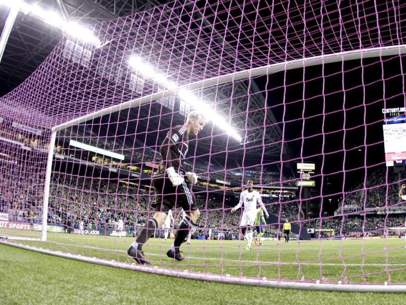 Playing in a pink net for breast cancer awareness, Vancouver Whitecaps goalkeeper David Ousted, left, steps back into the box after defending against a Seattle Sounders shot. (AP Photo)