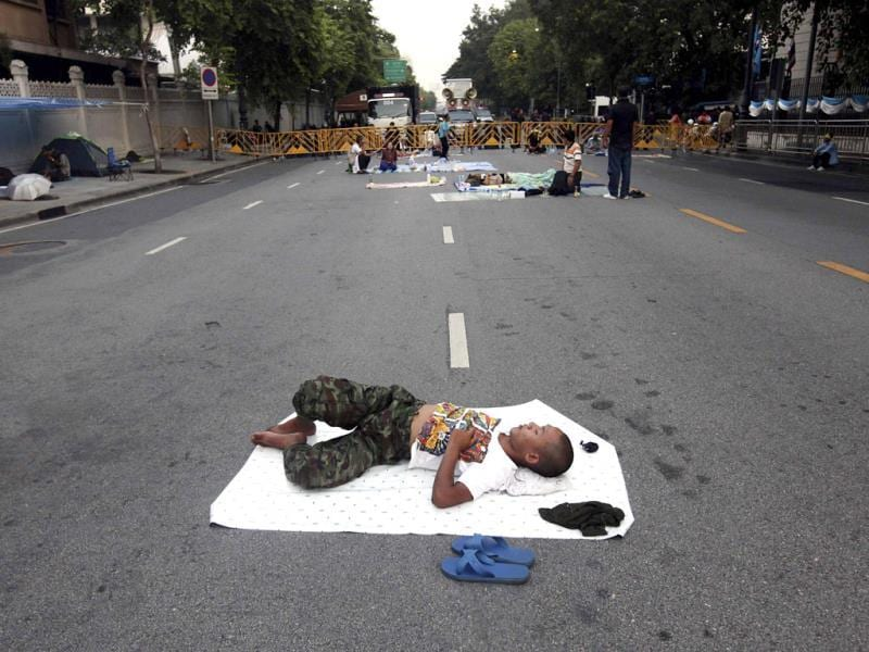An anti-government protester sleeps outside Government House in Bangkok. (Reuters Photo)