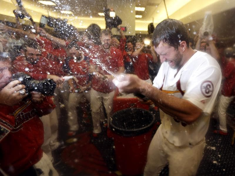 St Louis Cardinals pitcher Adam Wainwright sprays teammates in the locker room after the Cardinals defeated the Pittsburgh Pirates in a National League baseball division series. (AP Photo)