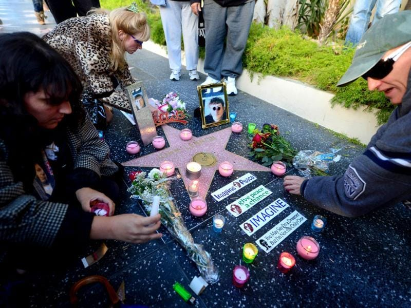 Nancy Hutchins (top) and fans place candles and flowers beside John Lennon's 'Star' along the Hollywood Walk of Fame in Hollywood, California. (AFP Photo)