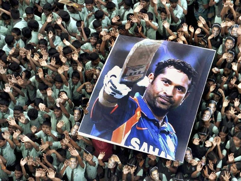 Students hold a large poster of Sachin Tendulkar after Tendulkar scored his landmark 100th international century. (AP Photo)