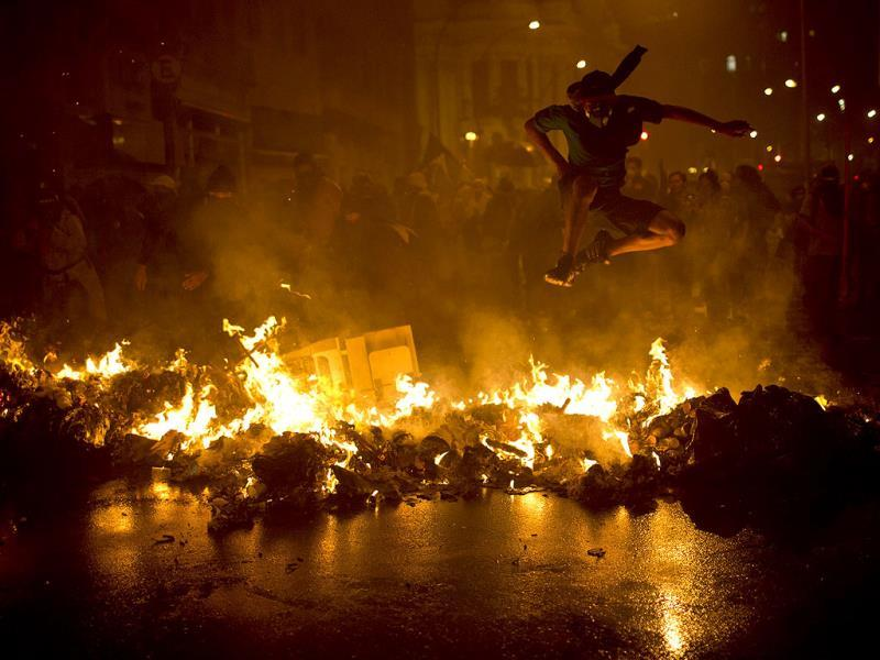 A demonstrator jumps over a burning barricade at the Cinelandia Square after violence erupted during a demonstration by teachers demanding higher pay, in Rio de Janeiro, Brazil. (AP Photo)