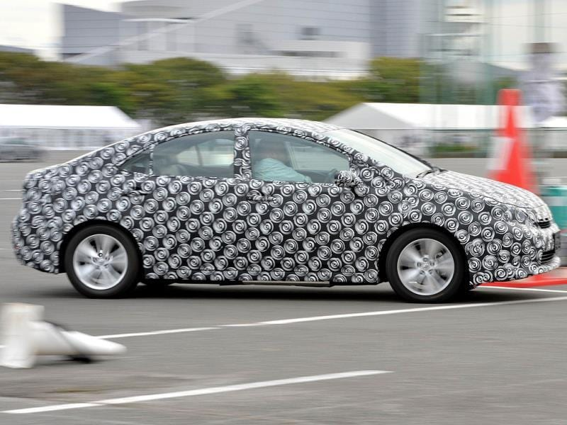 A prototype model of a fuel cell vehicle, covered with a camouflage masking sheet, in Tokyo. (AFP Photo)